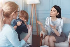 Psychologist talking with mother over her worries son. But can you understand the fact that. Young female professional trying to explain reasons of the worries Royalty Free Stock Photography