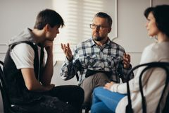 Psychologist talking to depressed teenager and his mum during therapy session stock image
