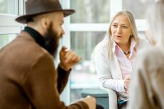Psychologist with young couple clients indoors. Senior female psychologist listening to the young couple clients during the psychologist therapy in the office royalty free stock images