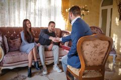 At the psychologist. Young couple sitting on couch, man greeting with doctor Stock Images