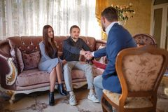 At the psychologist. Young couple sitting on couch, man greeting with doctor Stock Image