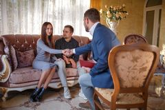 At the psychologist. Young couple sitting on couch, girl greeting with doctor Stock Photography