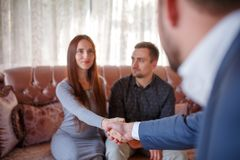 At the psychologist. Young couple sitting on couch, girl greeting with doctor Stock Image