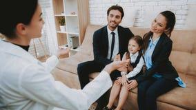 Psychologue Speaks avec la famille de sourire sur le sofa photos stock
