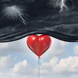 Psychology Of Human Love. Or a happy romantic feeling as an antidepressant as a red heart shaped balloon lifting up and away a dark storm cloud background as a Stock Photos