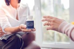 Psycholoog die een fles van slaappillen op een palm houden stock foto's