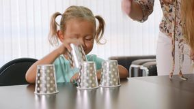 Psycholoog die weinig kindmeisje testen tijdens shell spel met koppen stock footage