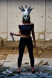 Psychopath killer with carneval mask holding knife in abandoned Stock Image