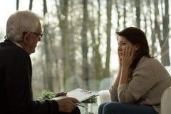 Psychotherapeut, der mit deprimierter Frau spricht Lizenzfreie Stockfotografie