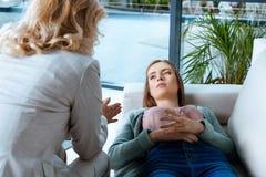 Psychotherapeut, der mit deprimierter junger Frau spricht Lizenzfreie Stockfotos