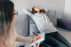 Psychotherapist молодой женщины профессиональный разговаривая с предназначенной для подростков девушкой в офисе Психические здоро стоковое изображение rf