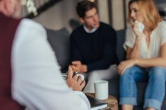 Psychotherapist counseling young couple. Psychologist consulting young couple in trouble. Psychotherapist taking down notes during counseling session stock image
