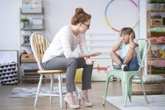 Psychotherapist die aan jong geitje spreken stock foto