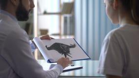 Psychotherapist die Rorschach-testkaart tonen aan vrouwelijke patiënt in kliniek, gezondheid stock videobeelden
