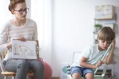 Psychotherapist showing picture to boy. Young psychotherapist showing a picture of house to a sad, orphaned boy Royalty Free Stock Image