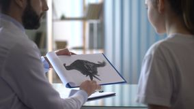 Psychotherapist showing Rorschach test card to female patient in clinic, health. Stock footage stock video footage
