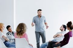 Psychotherapist speaking to difficult teenagers. Sitting in a circle in a white office with copy space Royalty Free Stock Photography