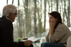 Psychotherapist talking with depressed woman royalty free stock photography