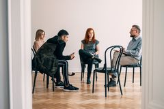 Psychotherapist talking to rebellious teenagers with alcohol add royalty free stock photography