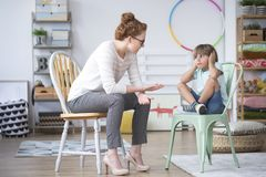 Psychotherapist talking to kid. Psychotherapist trying to talk to a difficult kid with hands on his ears stock photo