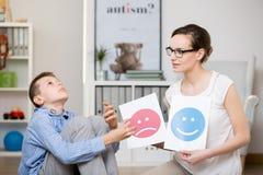 Psykolog som arbetar med den autistiska pojken royaltyfria foton