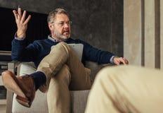 Psykolog som talar med patienten under terapin royaltyfria bilder