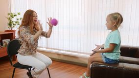 Psykolog som testar flickan för litet barn under bollspel stock video