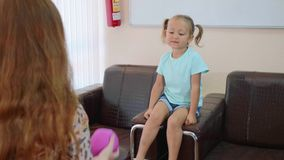 Psykolog som testar flickan för litet barn under bollspel arkivfilmer