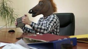 Psykopatkontorsanställd som framme bär en hästmaskering under arbetsdagsav datoren stock video