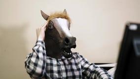 Psykopatkontorsanställd som framme bär en hästmaskering under arbetsdagsav datoren lager videofilmer