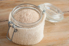 Psyllium husks powder. In glass jar over wooden rustic background Royalty Free Stock Images