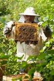 Pszczelarek spojrzenia przy ulem Miodowa kolekcja i pszczoły kontrola Fotografia Royalty Free