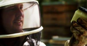 Pszczelarka trzyma butelkę beeswax zbiory