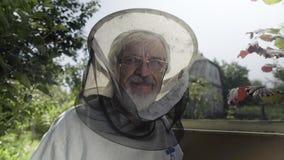 Pszczelarka w ochronnej przesłonie i kapeluszu jest przyglądającym kamerą i ono uśmiecha się zdjęcie wideo
