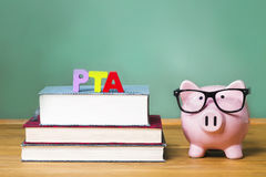 PTA theme with pink piggy bank with chalkboard. Parent Teacher Association theme with pink piggy bank with chalkboard in the background as concept image of the Royalty Free Stock Images