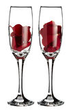 Pétalos color de rosa rojos dentro de 2 vidrios del champán Foto de archivo libre de regalías