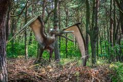 Pterodactyl dinosaur statue. Life sized Pterodactyl dinosaur statue in a forest royalty free stock photos