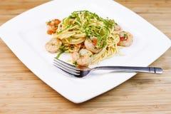 Pâtes avec la crevette et les herbes dans le plat blanc Image stock