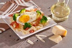 Pâtes de tagliatelles avec le brocoli, le prosciutto et l'oeuf au plat Images stock