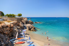 PTourists sunbathing and swimming in blue lagoon of Chora Sfakion town at Crete island, Stock Photos