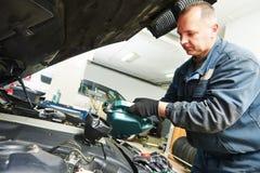 Pétrole se renversant de mécanicien de véhicule dans l'engine de moteur Image stock