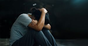 PTSD精神健康概念 岗位创伤重音混乱 沮丧的妇女单独坐在暗室backgr的地板 免版税库存图片
