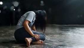 PTSD Mental health concept. Post Traumatic Stress Disorder. The depressed woman sitting alone on the floor in the dark room backgr. Ound. Film look stock images