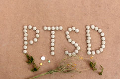 PTSD text with herbal pills on a wood background. Picture of a PTSD text with herbal pills on a wood background Stock Photos