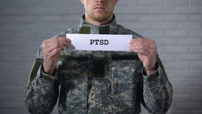 PTSD written on sign in hands of male soldier, posttraumatic disorder, health. Stock footage stock footage