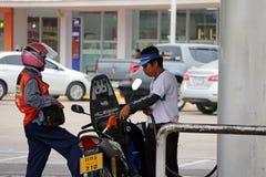 PTT加油站的换装燃料职员,刺激气体对摩托车 免版税库存照片