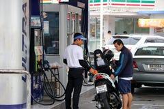 PTT加油站的换装燃料职员,刺激气体对摩托车 免版税库存图片