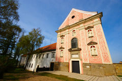 Ptuj, Domincan Monastery. Former Dominican Monastery in Ptuj, Slovenia with pink baroque façade with saints and park in spring stock image