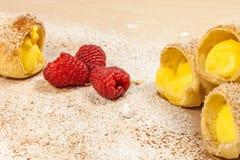 Ptysiowego ciasta custard waniliowi rogi i malinki na drewnianej desce Zdjęcia Royalty Free