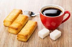 Ptysiowi ciastka, filiżanka z kawą, łyżka, cukrowi sześciany na stole obrazy royalty free